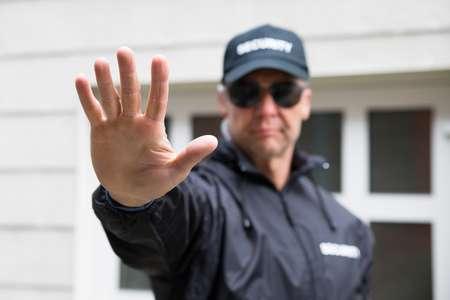 50245433-confía-en-la-toma-de-guardia-de-seguridad-gesto-de-la-parada-fuera-del-edificio